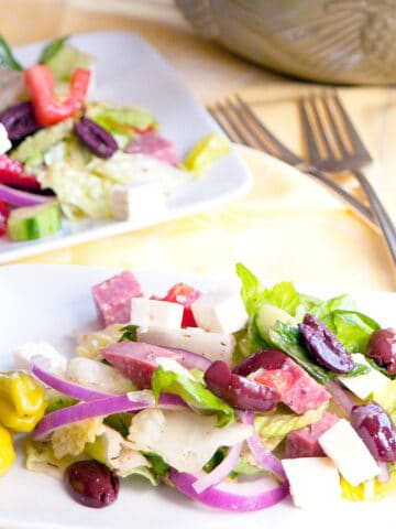A serving of Greek salad on a white plate with two forks and a bowl in the background.