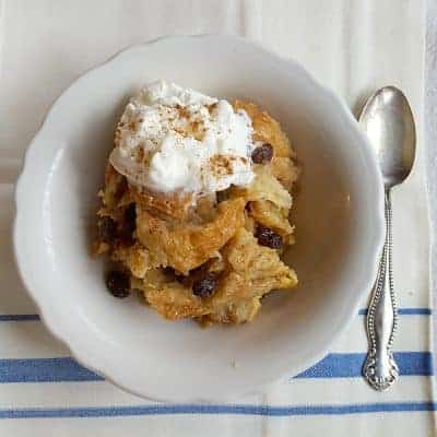 Slow Cooker Bread Pudding - creamy and luscious made with French bread and studded with raisins. From @NevrEnoughThyme https://www.lanascooking.com/slow-cooker-bread-pudding/
