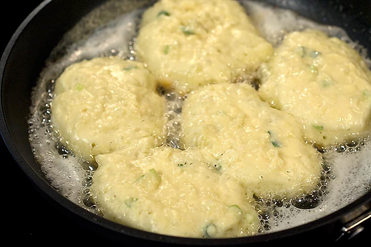 Potato pancakes frying in oil in a skillet
