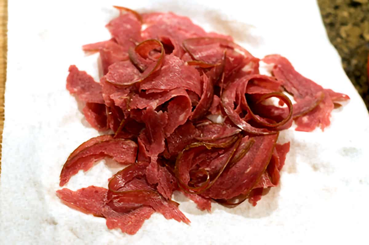 Dried beef draining on a paper towel after being shredded and rinsed.