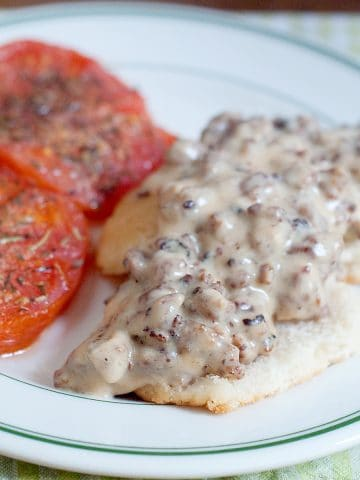 Sausage Gravy and Biscuits with Tomatoes - A hearty country breakfast of sausage gravy served over biscuits with baked, herbed tomato slices on the side. From @NevrEnoughThyme https://www.lanascooking.com/sausage-gravy-and-biscuits-with-tomatoes/
