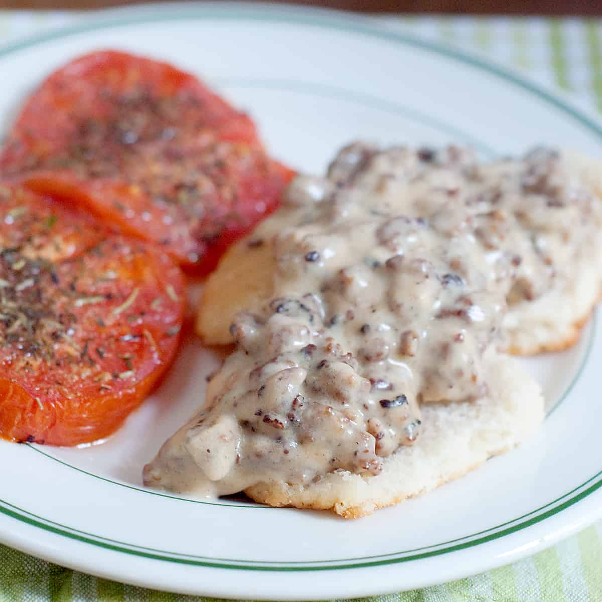 Sausage Gravy and Biscuits with Tomatoes - A hearty country breakfast of sausage gravy served over biscuits with baked, herbed tomato slices on the side. https://www.lanascooking.com/sausage-gravy-and-biscuits-with-tomatoes/