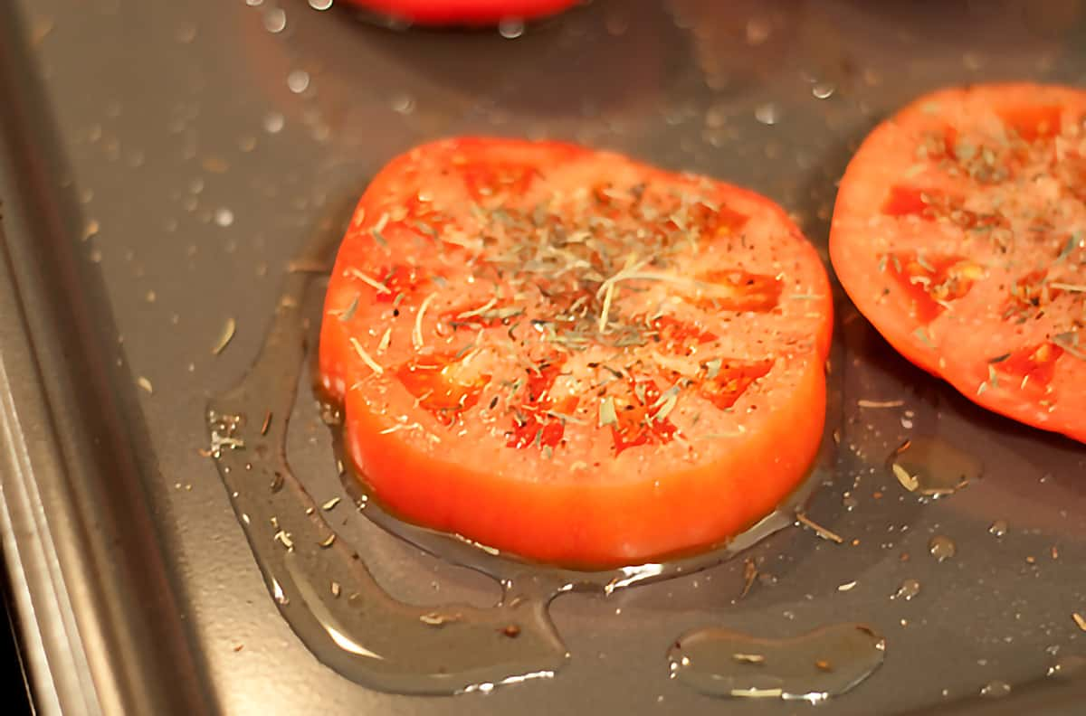 Tomato slices drizzled with oil and sprinkled with herbs on a baking sheet.