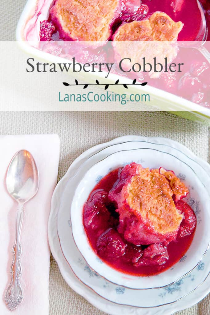 A serving of strawberry cobbler in a china dish with a spoon and napkin alongside.