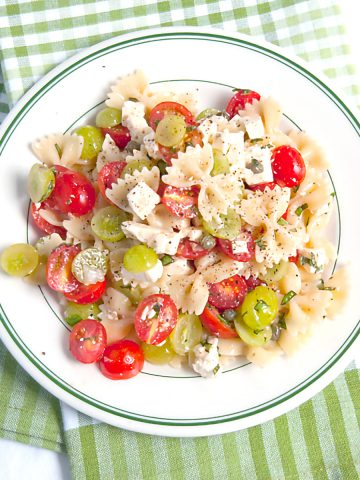 Bow Tie Pasta Salad with Tomatoes and Grapes - a surprising combination for a refreshing summery pasta salad. Great for a cookout or picnic! https://www.lanascooking.com/bow-tie-pasta-salad-with-tomatoes-and-grapes/