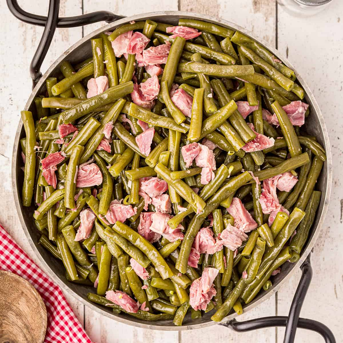 Old Fashioned Southern Style Green Beans with ham hocks in a serving dish on a tabletop.