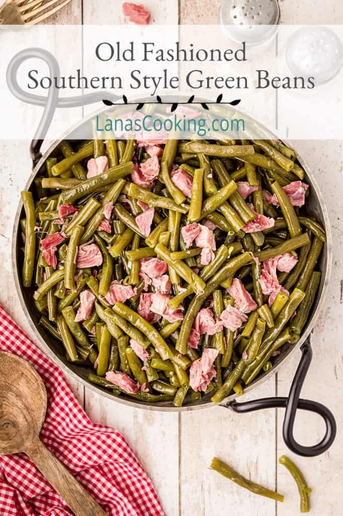 Old Fashioned Southern Style Green Beans with ham hocks in a serving dish on a tabletop. Text overlay for pinning.