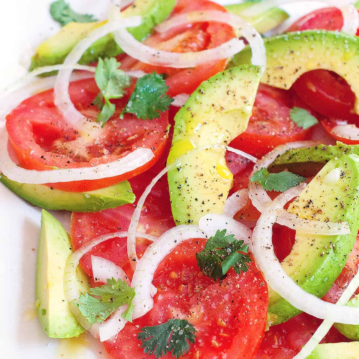 Tomato and avocado salad on a large white serving plate.
