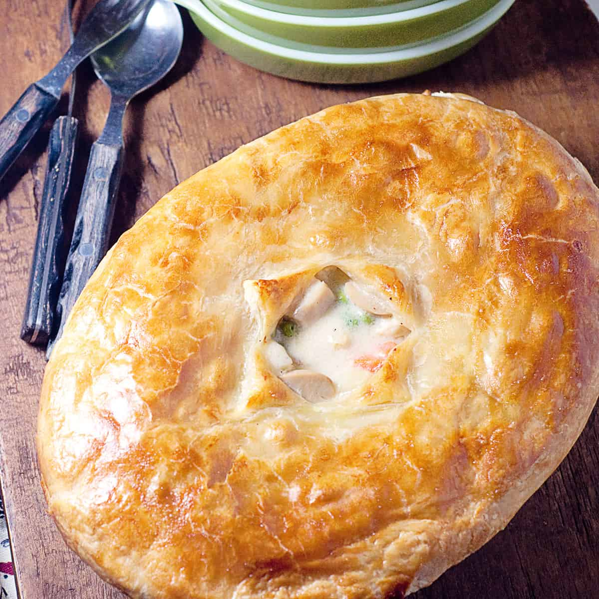 Classic chicken pot pie in a serving dish on a wooden board.