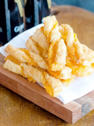Puff Pastry Cheese Straws mounded on a serving board.