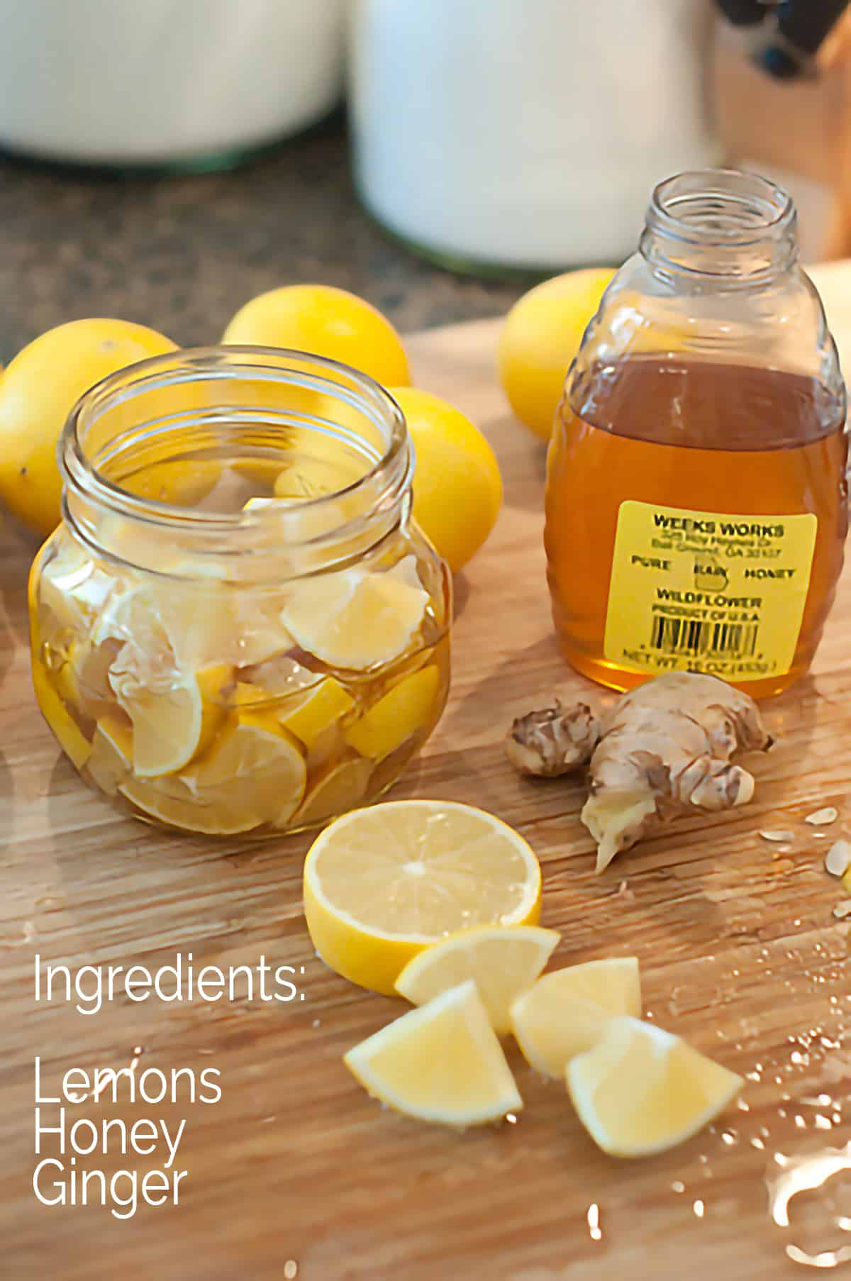 The Lemon, Honey, and Ginger Throat Soother being assembled: a jar containing lemon wedges and grated fresh ginger with honey poured over everything.