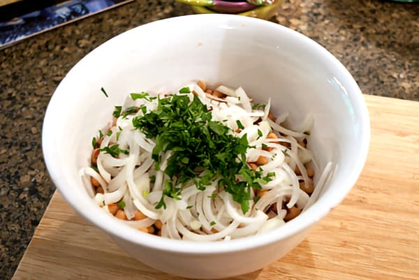 Black eyed peas, onion, and fresh chopped parsley in a mixing bowl