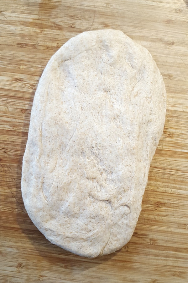 Half of dough flattened into a rectangle.