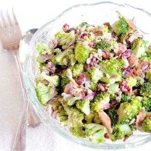Broccoli Salad in a glass serving bowl with vintage serving utensils.