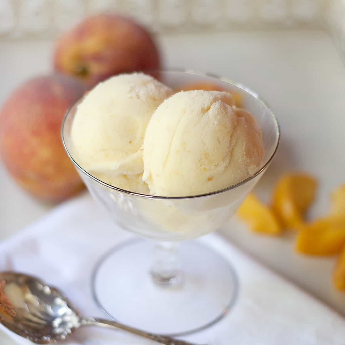 Creamy, cold and delicious homemade peach ice cream with sweet, fresh Georgia grown peaches and rich with eggs, heavy cream, and whole milk. From @NevrEnoughThyme https://www.lanascooking.com/homemade-peach-ice-cream/