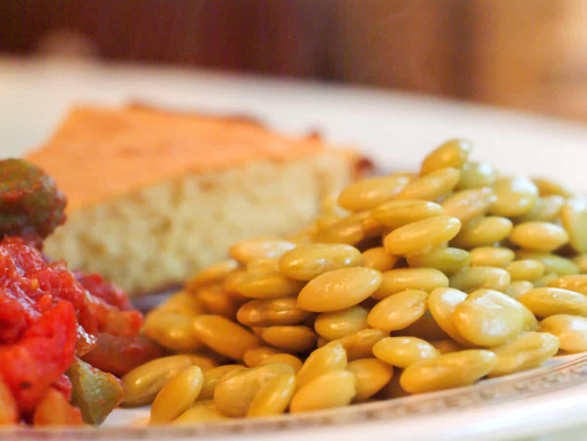 A dinner plate with cooked butter beans, tomatoes with okra, and cornbread.