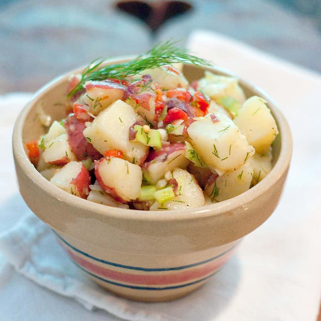 Lemon Dill Potato Salad - A warm potato salad dressed with a mixture of olive oil, lemon, and dill. No mayo makes it safer for picnics! https://www.lanascooking.com/lemon-dill-potato-salad/