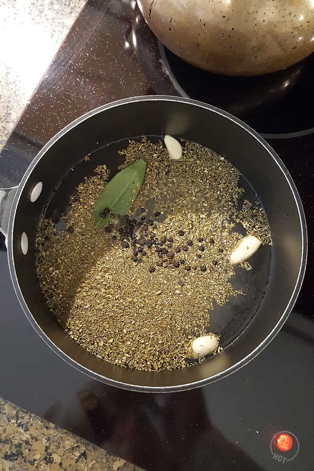 Brine ingredients for quick pickled jalapenos in a saucepan on a stovetop