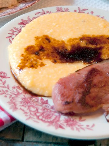 Country Ham with Red Eye Gravy - Salty, dry cured country ham with red eye gravy flavored with strong black coffee served with a side of cheese grits. From @NevrEnoughThyme https://www.lanascooking.com/country-ham-with-red-eye-gravy/