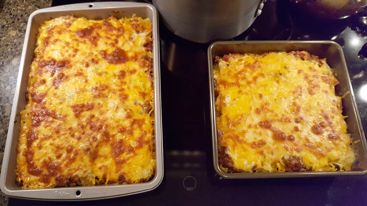 The two pans of lasagna after baking sitting on the stovetop to cool before serving.