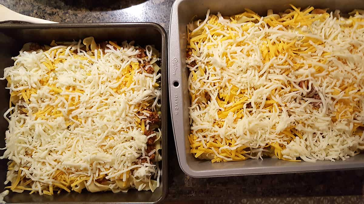 Two pans (one 9x9 and one 9x13) filled with the assembled egg noodle lasagna.