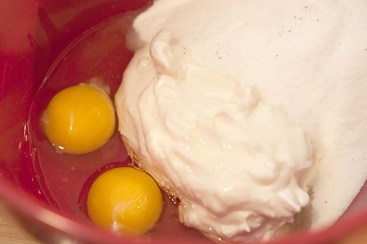 Sour cream, sugar, eggs, and vanilla in a mixing bowl.