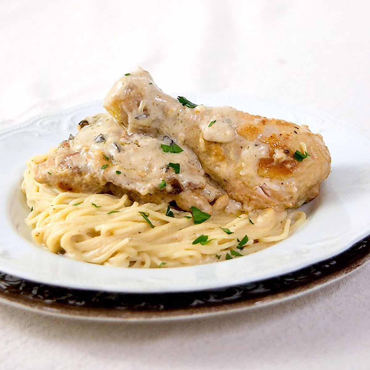 Delicious Baked Parmesan Chicken with a creamy mushroom and Parmesan sauce over angel hair pasta is a simple and delicious dinner that the entire family will enjoy.  @NevrEnoughThyme https://www.lanascooking.com/baked-parmesan-chicken