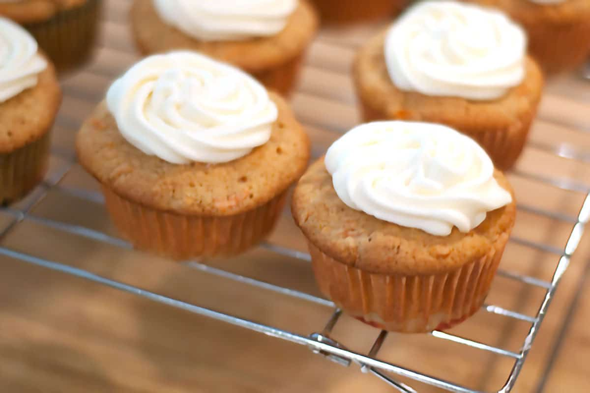 Baked cupcakes sitting on a cooling rack with cream cheese frosting piped on top of each cupcake.