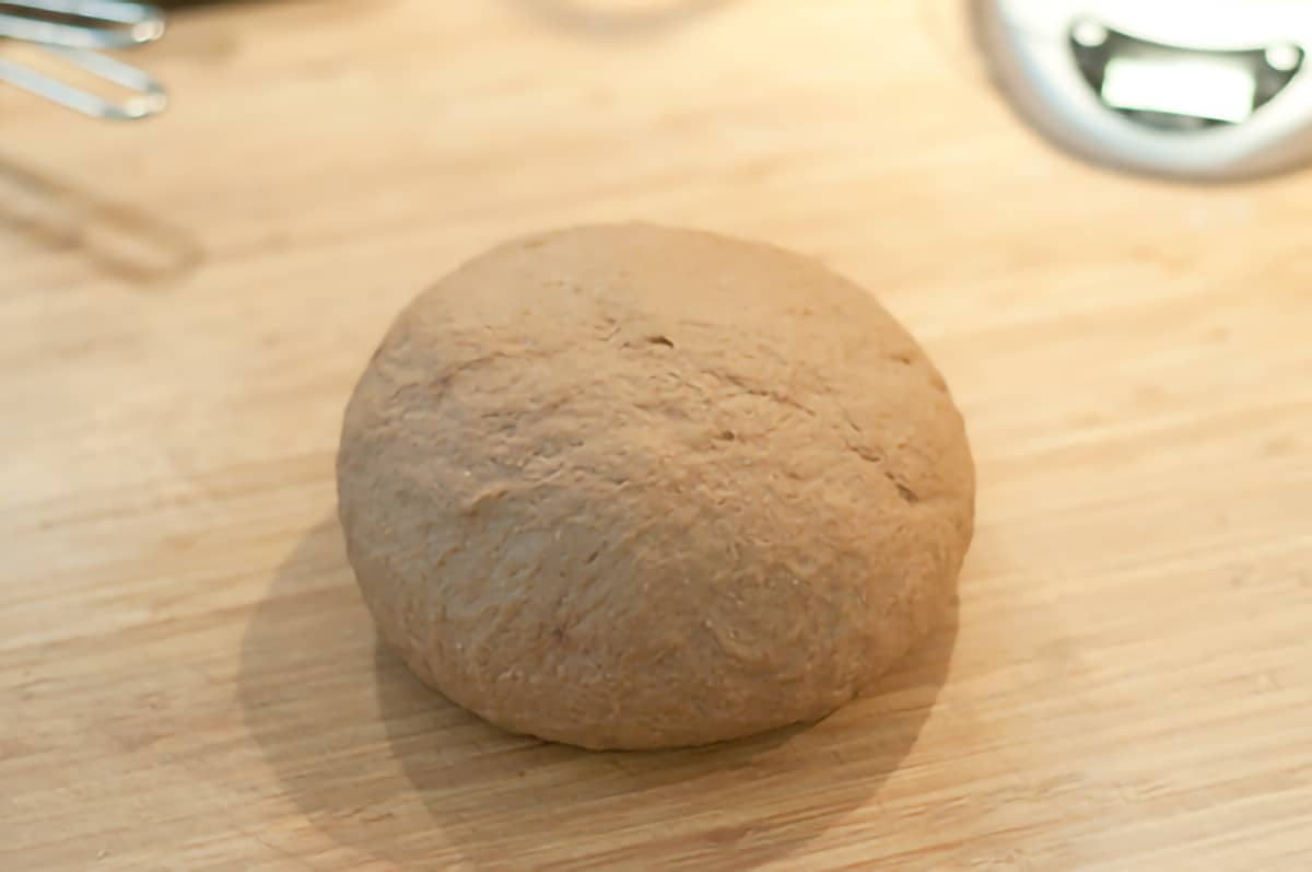 Ball of kneaded dough sitting on a cutting board