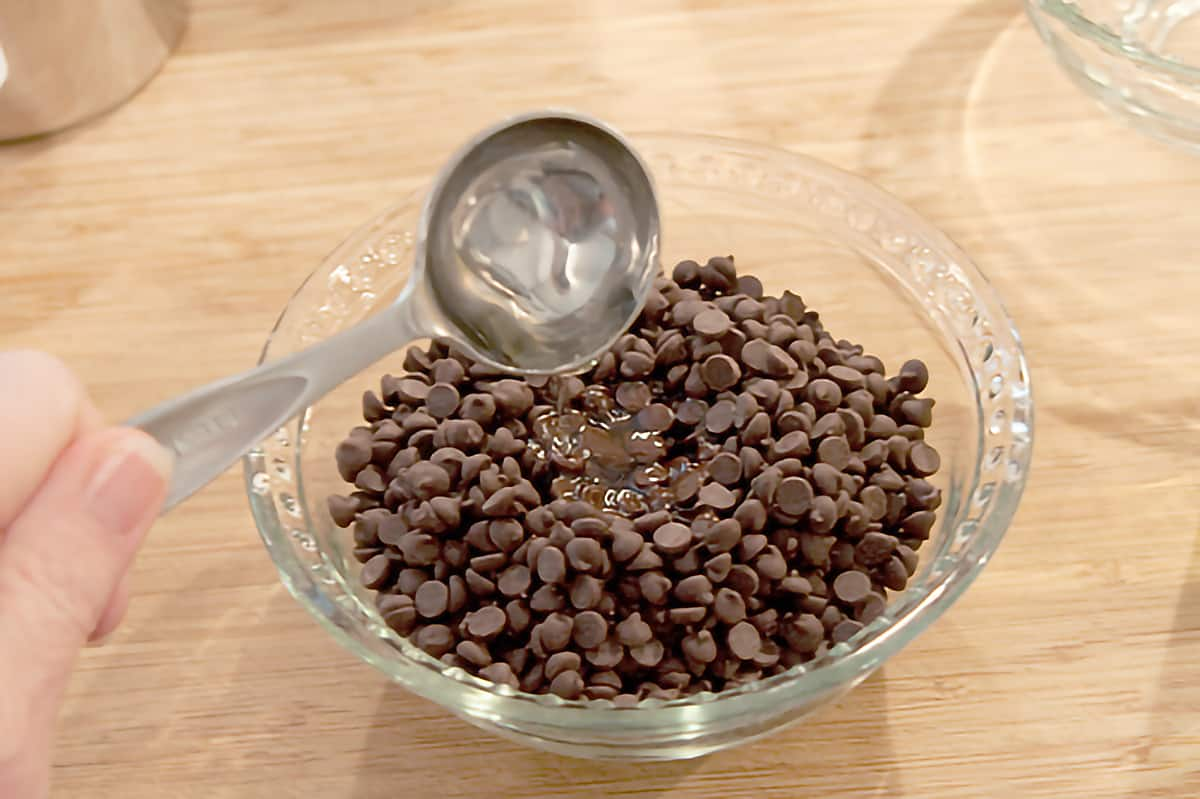 Small bowl containing chocolate chips; oil being added with a measuring spoon.