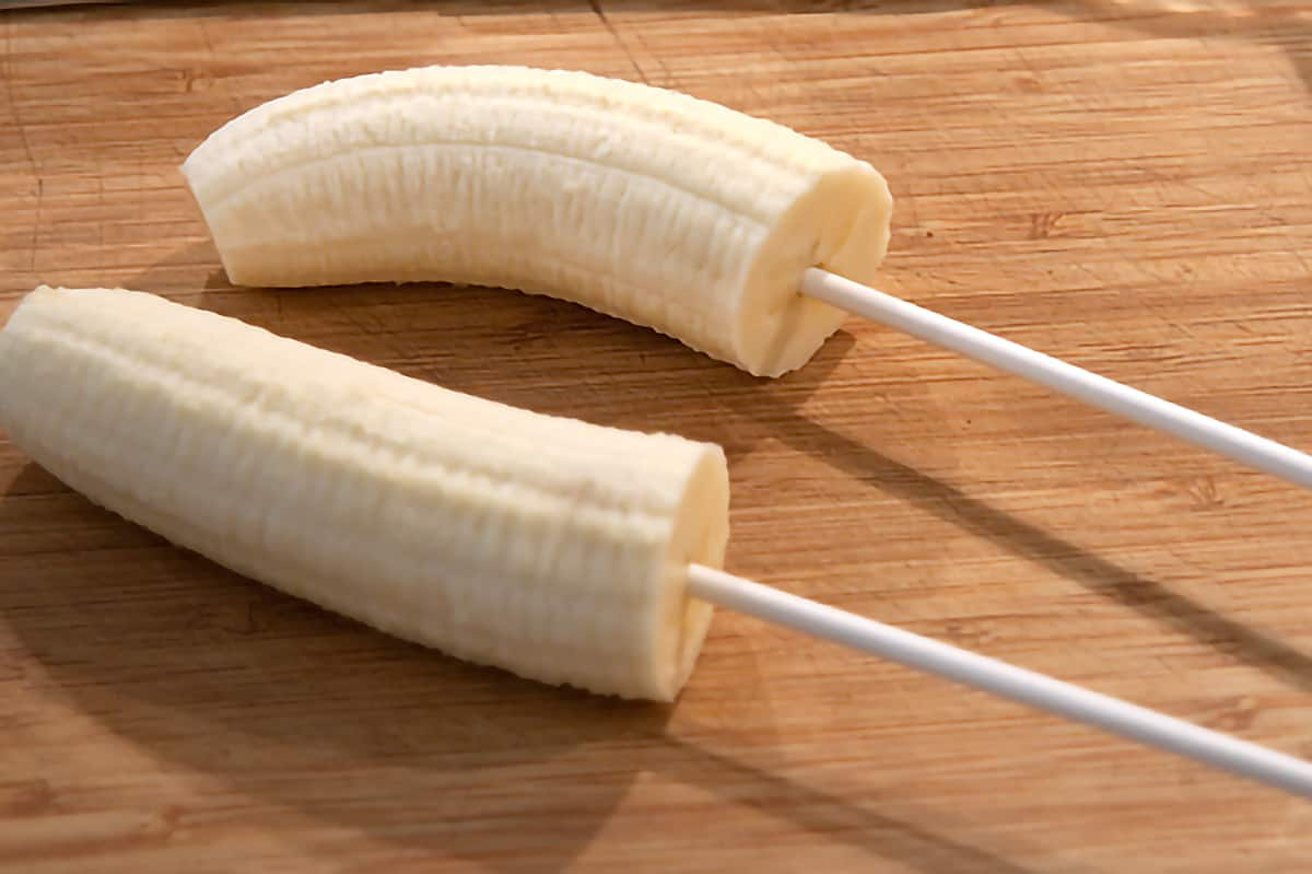 Two banana halves with lollipop sticks inserted.