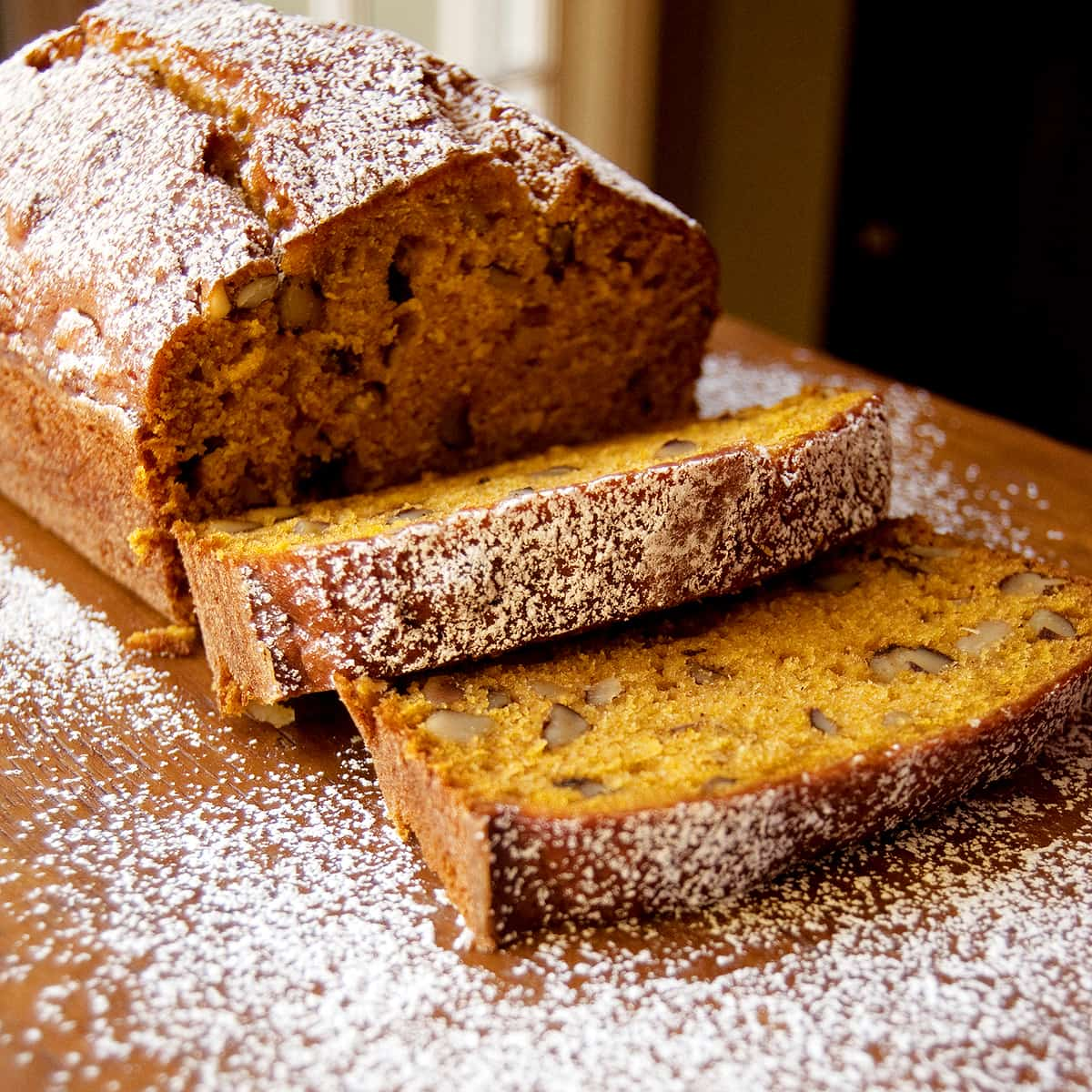 Sliced black walnut pumpkin bread on a serving board.