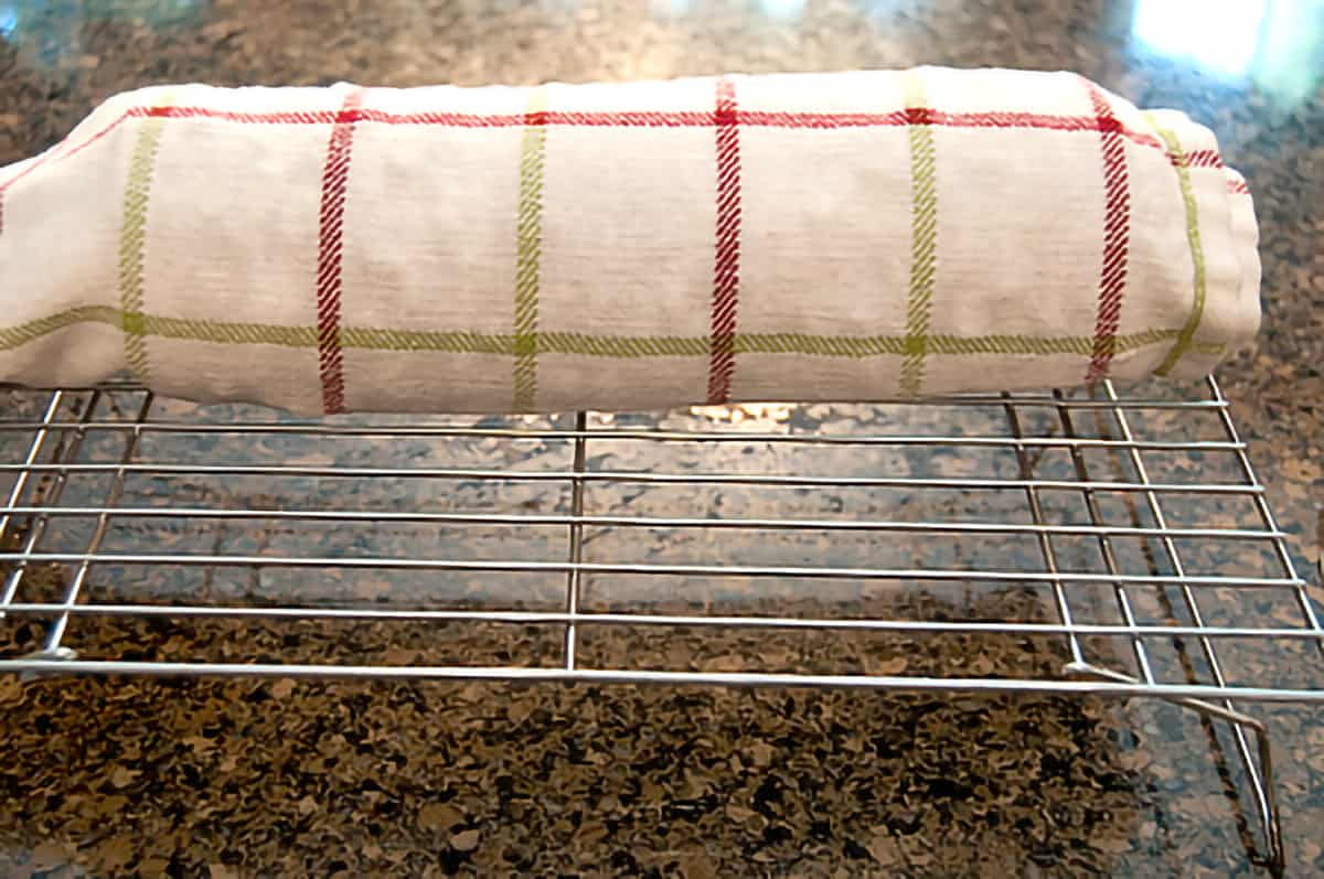 Cake rolled in a tea towel resting on a metal cooling rack.