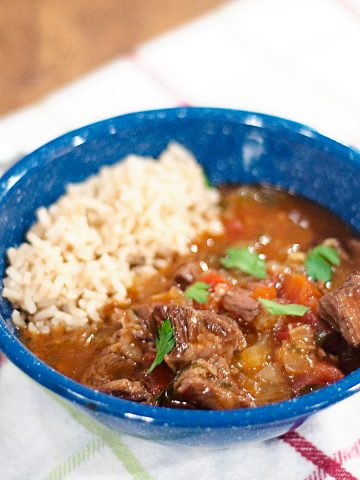 A serving of Garlicky Beef Stew with brown rice in a blue bowl.