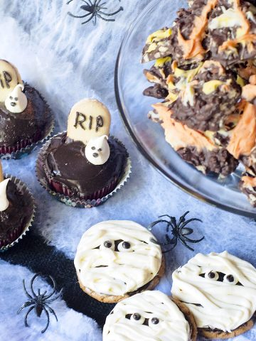 Ghosts in the Graveyard cupcakes, Mummy Cookies, and Candy Corn Bark on a spiderweb background.