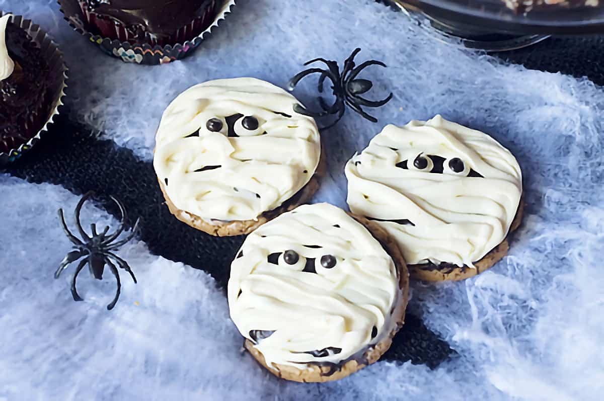 Three mummy cookies on a spiderweb background