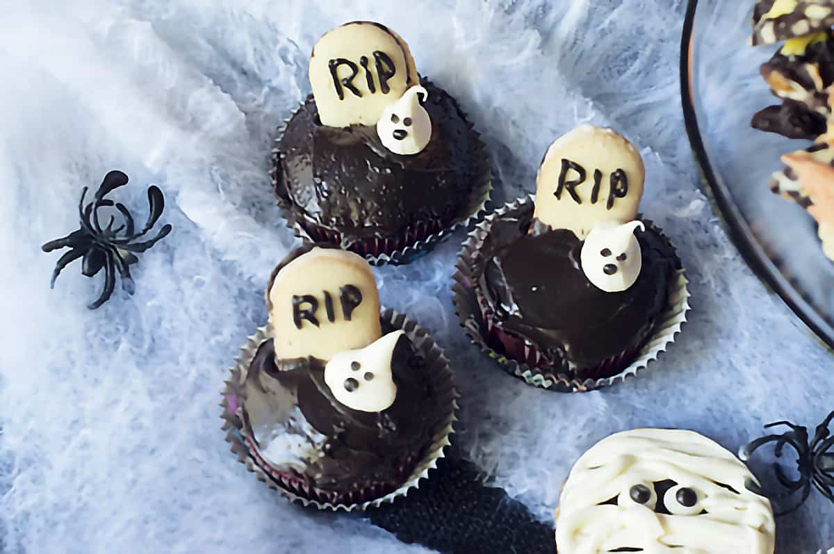 Chocolate cupcakes with tombstone and ghost decorations on a spiderweb background