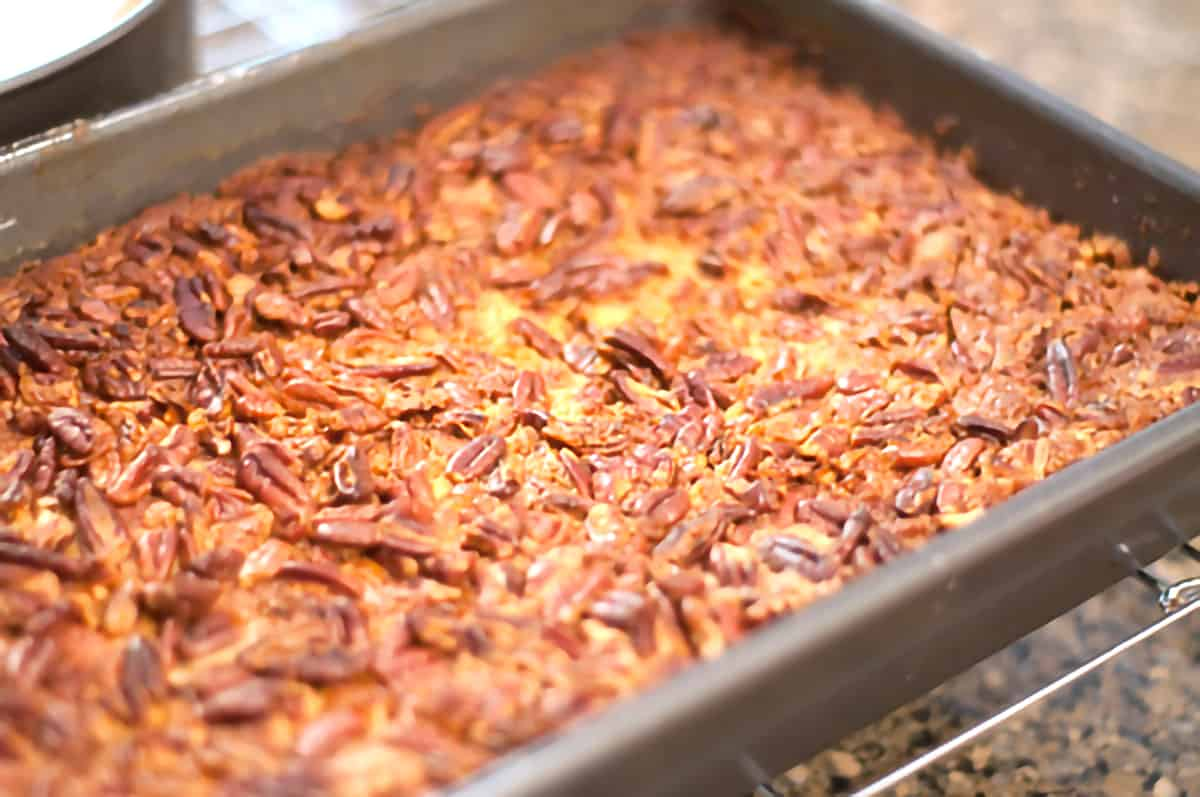 Baked Pumpkin Pecan Crunch Cake cooling in pan on a cooling rack.