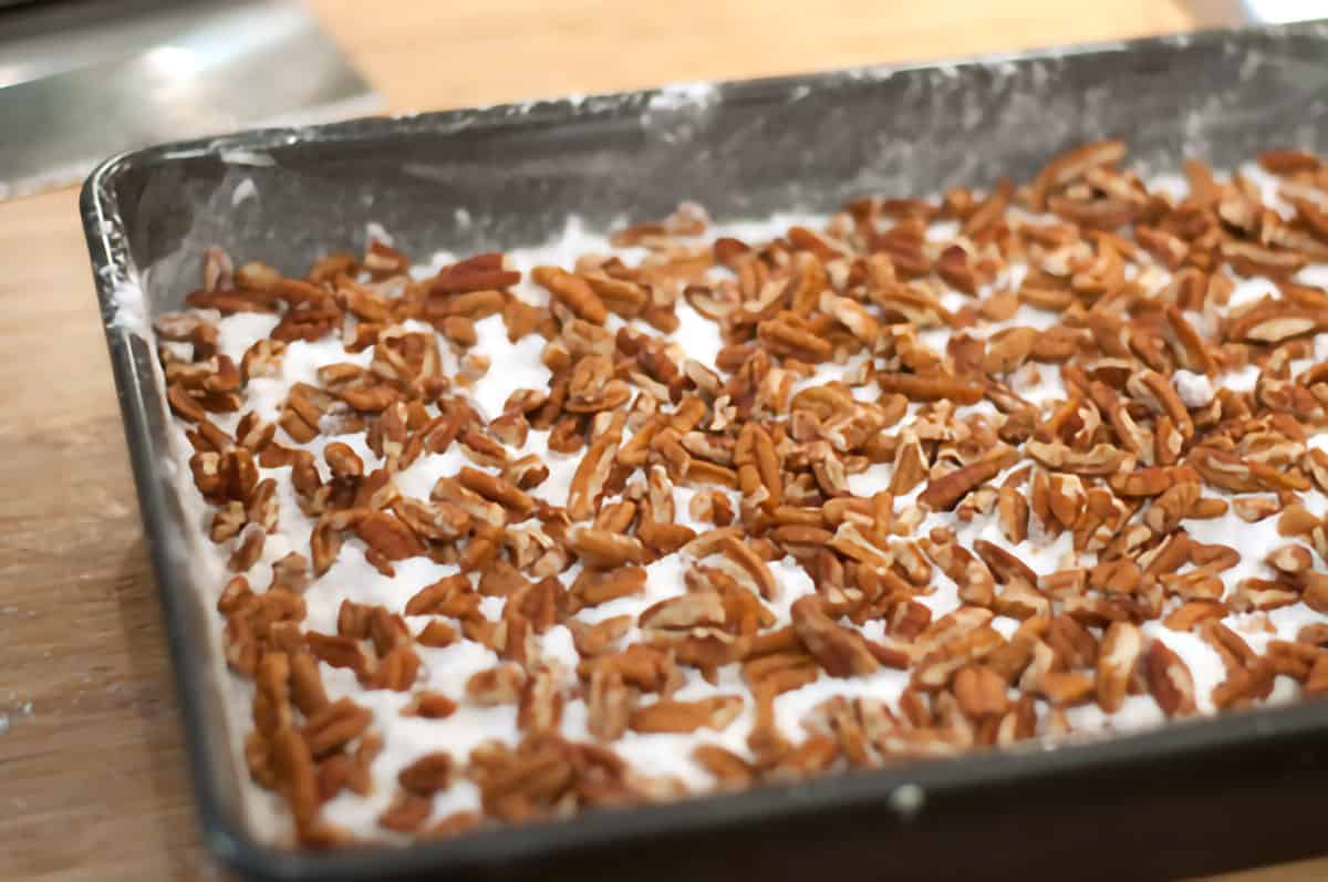 Chopped pecans sprinkled over dry cake mix in a baking pan.