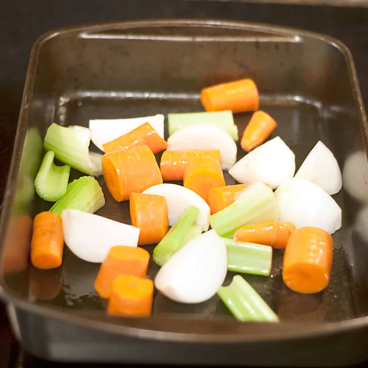 A baking pan containing carrots, onions, and celery.