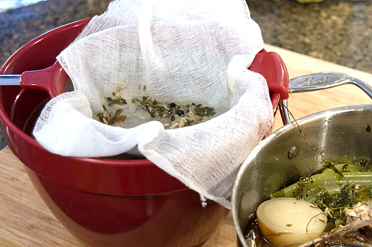 A red bowl holding a strainer lined with cheesecloth for straining broth.