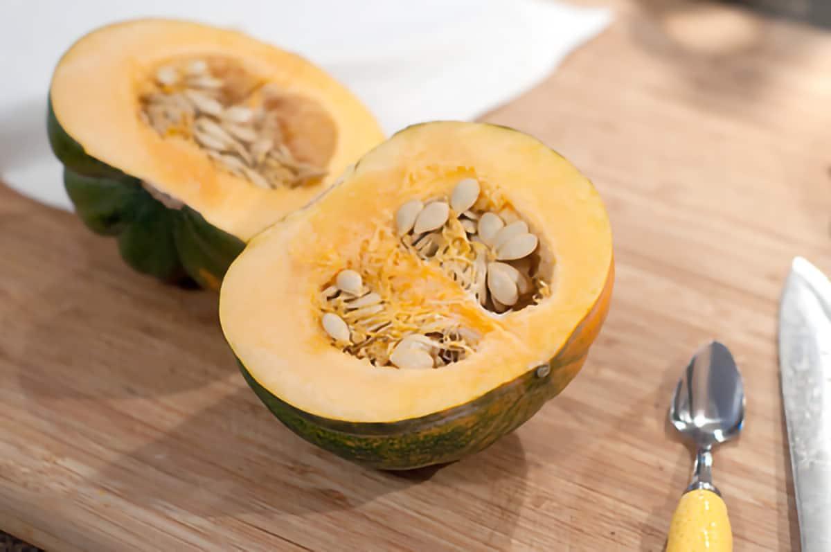 A halved acorn squash on a cutting board.