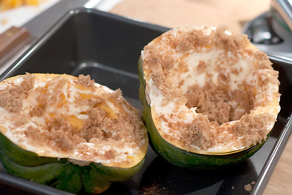 Halved acorn squash interior sides coated with butter and brown sugar.