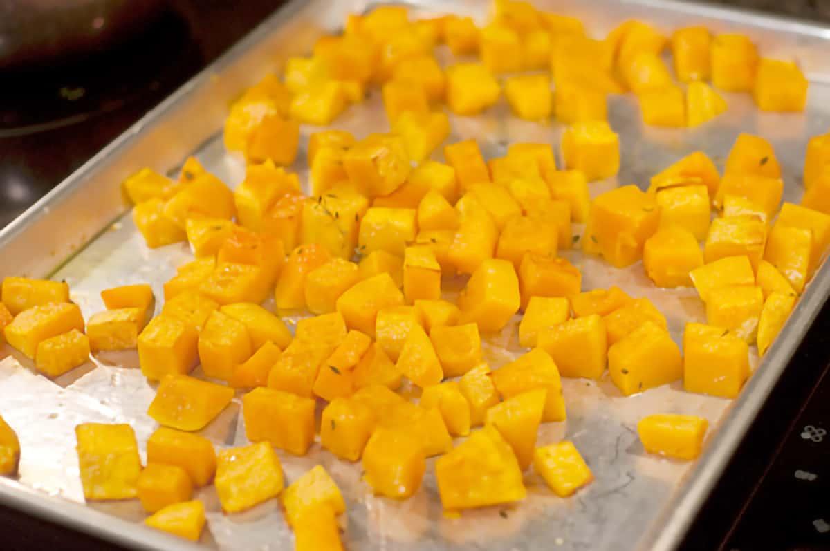 Roasted butternut squash cubes on a baking sheet.