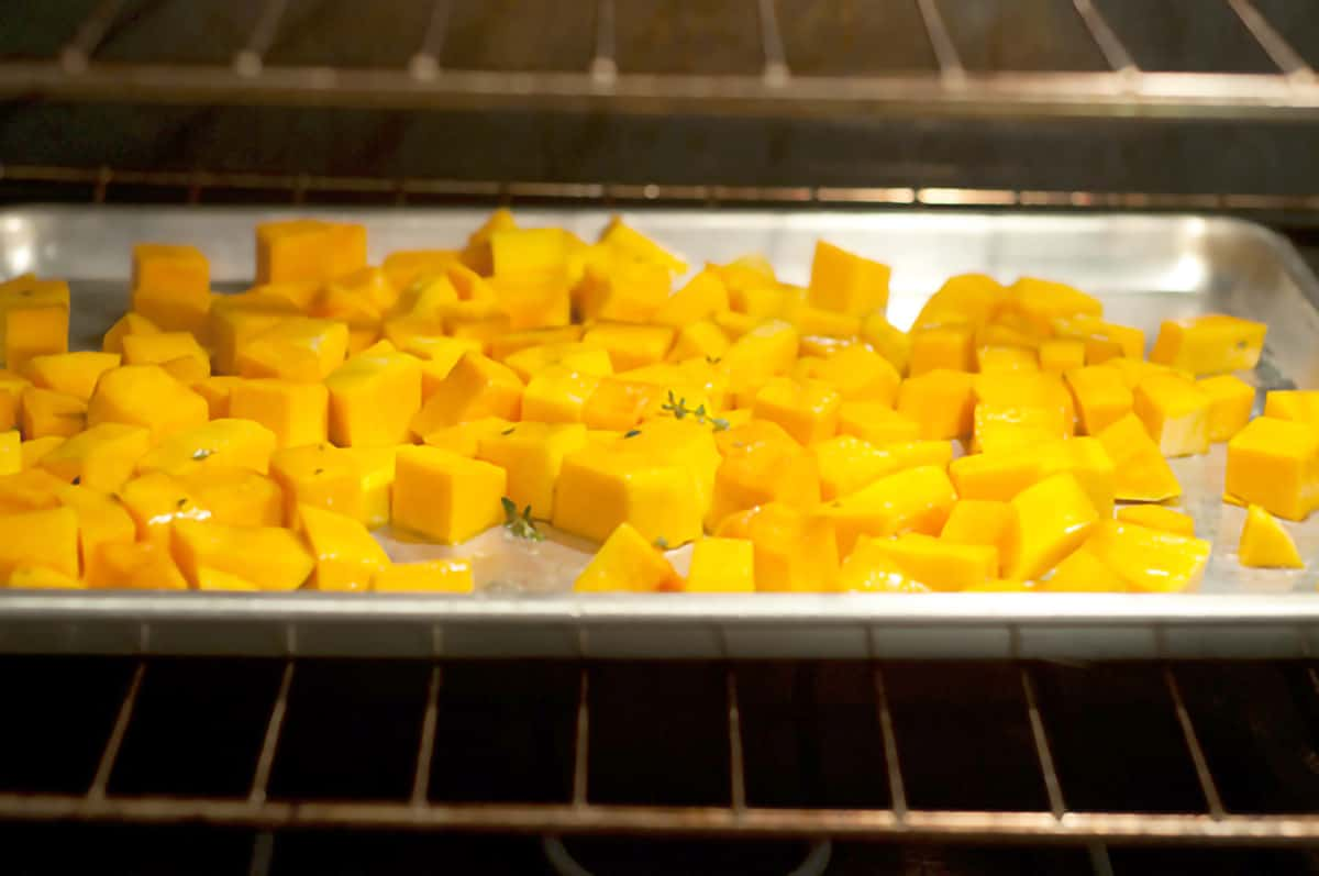 One-inch cubes of butternut squash on a baking sheet.