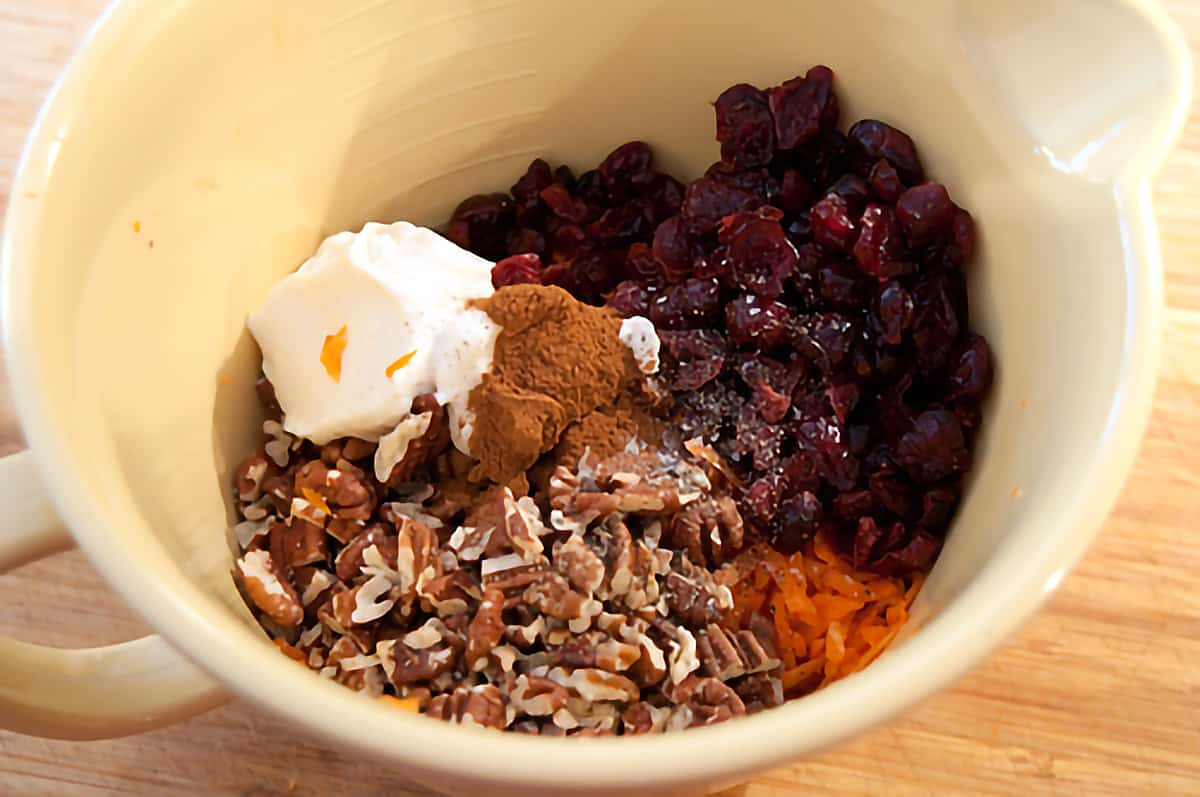 All ingredients for the Carrot Cranberry Salad in a mixing bowl.