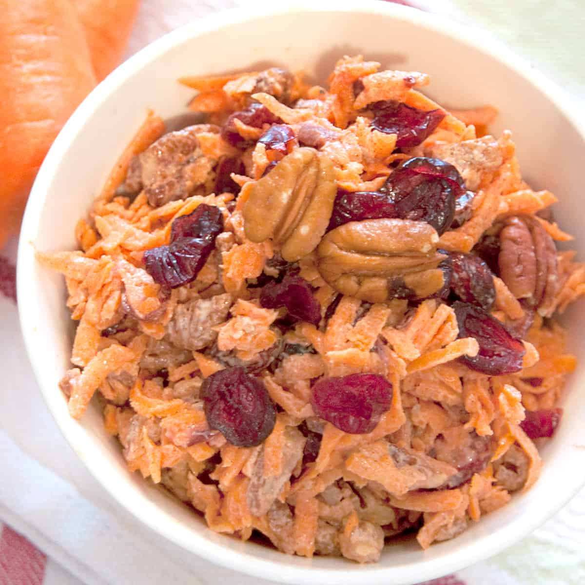 Carrot Cranberry Salad in a serving bowl on a kitchen towel.