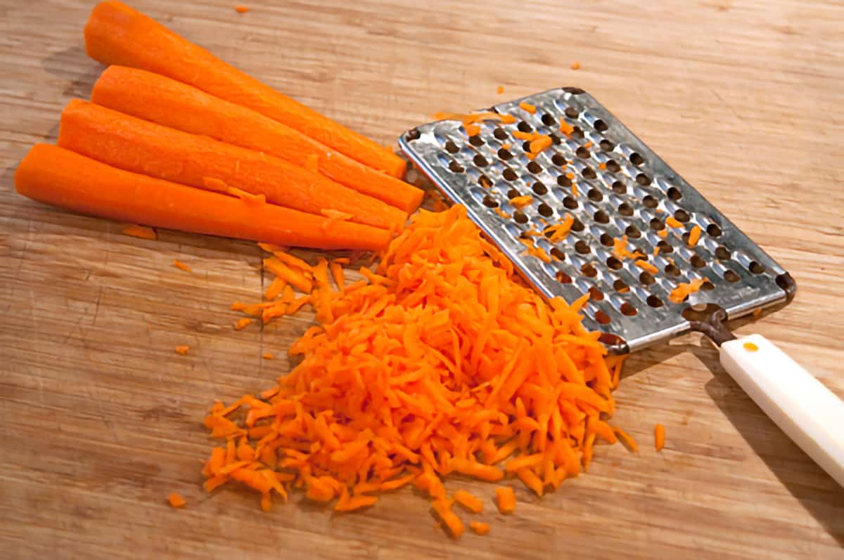 Grated carrots and a grater on a cutting board.