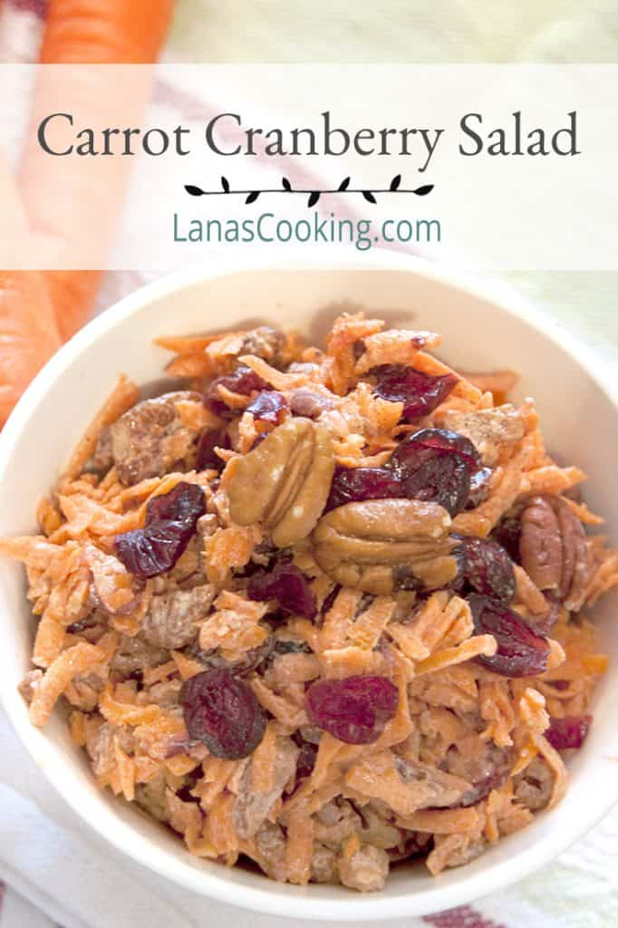 Carrot Cranberry Salad in a serving bowl on a kitchen towel. Text overlay for pinning.