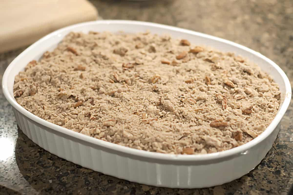 Gingerbread, sugar, and pecan mixture sprinkled over baking dish filled with apple pie filling and gingerbread.
